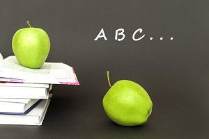 letters a,b,c, two green apples, open books with concept