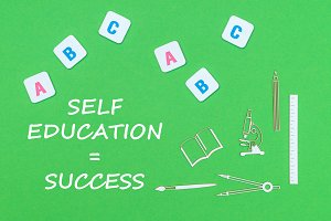 text self education success, from above wooden minitures school supplies and abc letters on green background