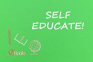 text self educate, school supplies wooden miniatures on green background