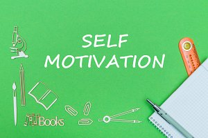 text self motivation, school supplies wooden miniatures, notebook with ruler, pen on green backboard