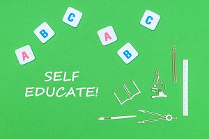text self educate, from above wooden minitures school supplies and abc letters on green background