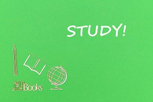 text study, school supplies wooden miniatures on green background