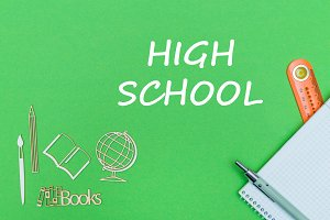 text high school, school supplies wooden miniatures, notebook on green background