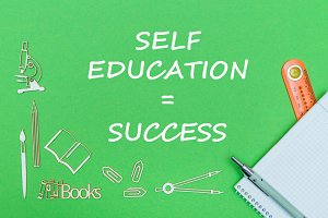 text self education success, school supplies wooden miniatures, notebook with ruler, pen on green backboard