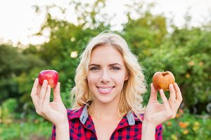 Beautiful woman holding rotten and good apple