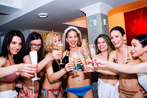 Cheerful bride and bridesmaids celebrating hen party with champa