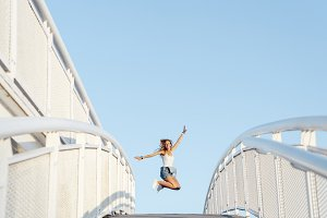 Woman jumping over a bridge