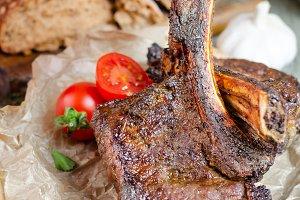 Rib eye beef steak on wooden plate.
