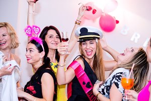 Cheerful bride and bridesmaids celebrating hen party with drinks