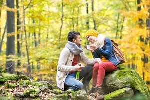 Beautiful couple in autumn forest, thermos and cup