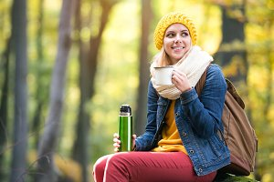 Beautiful woman in autumn forest, thermos and cup