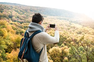 Unrecognizable man with smart phone against colorful autumn fore