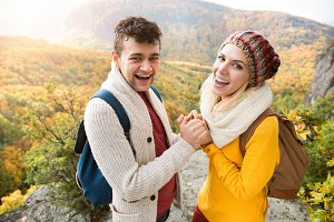 Beautiful couple in autumn nature against colorful autumn forest