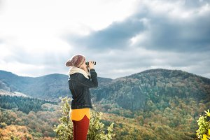 Beautiful woman looking through binoculars, colorful sunny autum