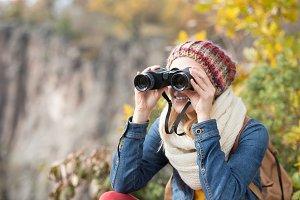 Beautiful woman looking through binoculars, colorful sunny autum