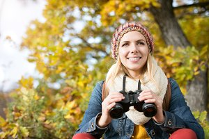 Beautiful young woman holding binoculars, colorful sunny autumn
