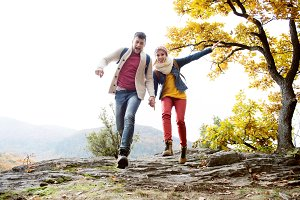 Beautiful couple in sunny autumn nature, running on a rock