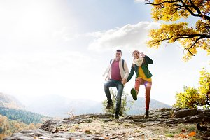 Beautiful couple in sunny autumn nature, jumping on a rock