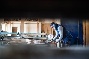 A man worker in the carpentry workshop, working with wood.