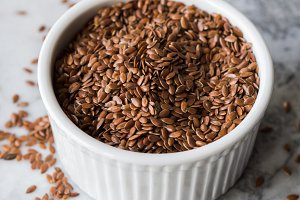 Flax seeds in ramekin on marble board