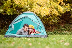 Beautiful couple lying in tent, camping in autumn nature