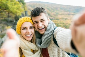 Young couple on a walk in autumn forest taking selfie