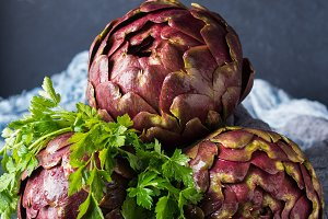 Raw artichokes with parsley on dark background