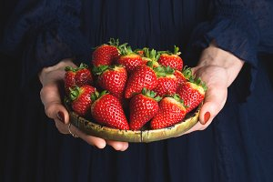 Dish of strawberries in hands of a woman
