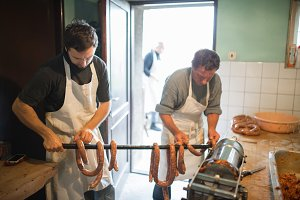Two men hanging homemade raw sausages on wooden stick.