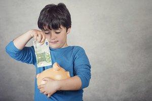 child saving money in a piggy bank