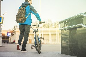 male teenager walking in the city with bmx  portrait