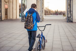 young teenager in the city with bicycle with backpack