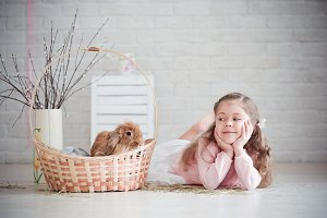Girl lies near a basket with rabbit