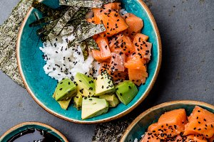 Salmon sushi bowl or salmon poce with soy sauce. Top view. Gray slate background