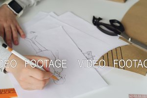 Tilt up of Fashion designer is drawing lines on clothing sketch with coffee, tailor's scissors, ruler and pieces of paper on studio table. Attractive girl is busy and concentrated on work.