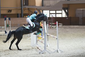 Young woman on the black stallion jumping over hurdle at show jumping competition