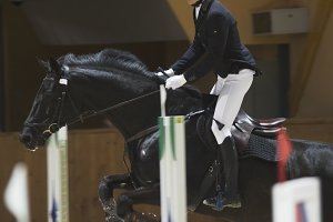Young rider on black horse galloping at show jumping competition