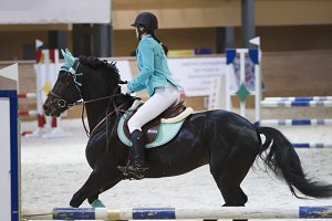 Slim young woman on the black horse galloping at show jumping competition