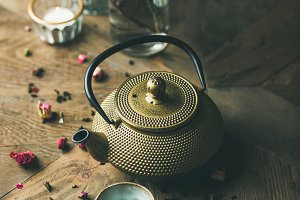 Golden iron teapot, cups, dried rose, candles and almond flowers