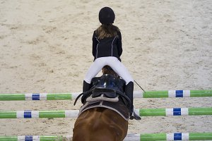 Young child girl rider jumping on the horse over obstacle at show jumping competition