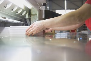 Female worker folds a stack of paper in the typography