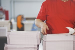 Female worker typography turning pages of a printed magazine