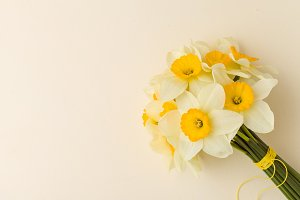 White daffodil bouquet on yellow pastel background with copy space.