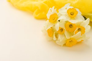 White daffodil bouquet with yellow textile decoration on pastel background with copy space.