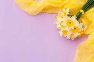 Daffodil bouquet with yellow textile decoration on violet pastel background with copy space.