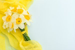 Daffodil bouquet with yellow textile decoration on blue pastel background with copy space.