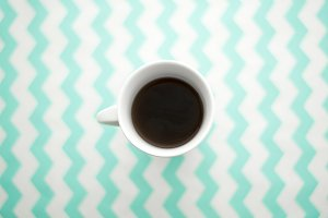 Coffee on turquoise desk