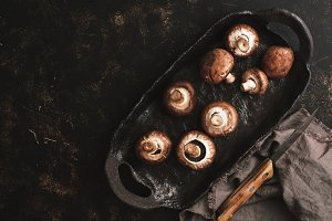 Mushrooms on a rustic ceramic tray, dark brown background. Top view, copy space. Country style.