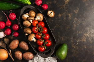 Varied vegetables and mushrooms on a rustic ceramic dish. The concept of healthy eating. Dark brown background, top view, copy space.