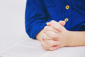 The child prays. Selective focus.